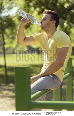 Athlete relaxing after an intense workout drinking water