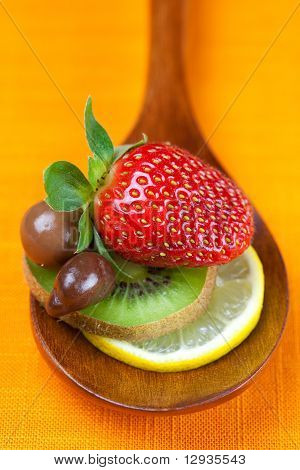 Strawberries, Kiwi And Chocolate Candy In The Wooden Spoon Of The Orange Fabric