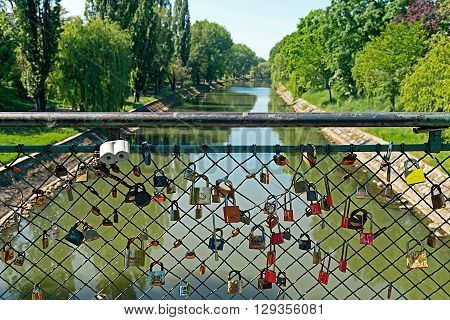 TIMISOARA ROMANIA - MAY 06 2016: Bridge with lovers locks symbol of loyalty and eternal love over the Bega River in Timisoara.