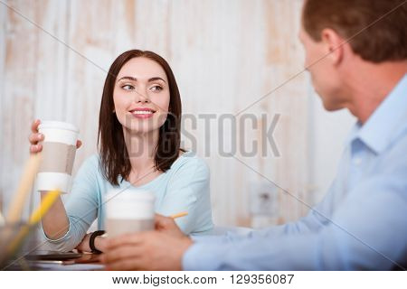 My break. Smiling and positive young people sitting at the table and drinking coffee while talking with each other during the day