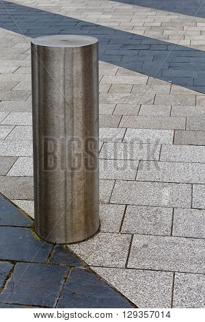 Stainless Steel bollard on grey pavement with a few lines of dark grey paving slabs