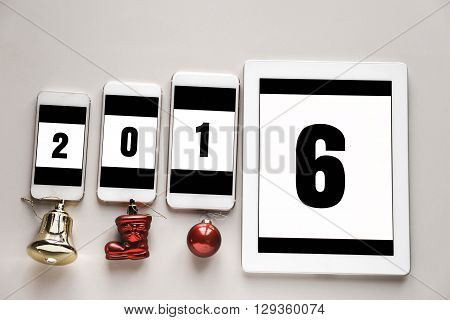 2016 writing on smart phone screens. Black numbers on a white background. Christmas ornaments below. Overhead shot.