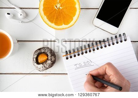 Hand writing to do list with black pen white wooden table chocolate cookie smart phone slice of orange earphones carrot juice around