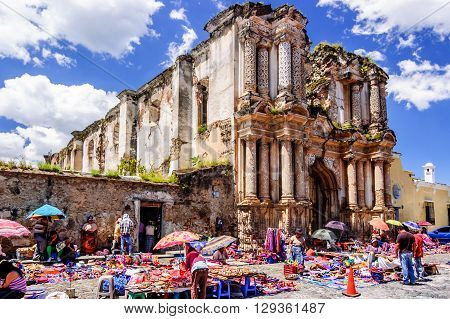 Antigua Guatemala - October 4 2014: Weekend Mayan textile market in cobblestone street outside El Carmen ruins in colonial city & UNESCO World Heritage Site of Antigua.