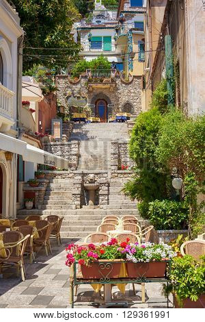 TAORMINA SICILY - MAY 11 2012: Restaurants with stone steps in Taormina Italy. Taormina is the most beautiful city in Sicily.