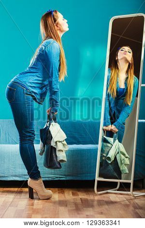 Fashion and shopping. Woman in full length wearing denim with bag. Attractive female shopper looking in mirror standing in clothes store. Blue color