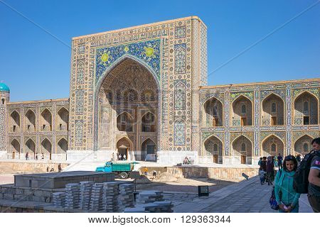 Samarkand Uzbekistan - April 18 2014: People in Registan square with the Tilla Kari madrassah in the background