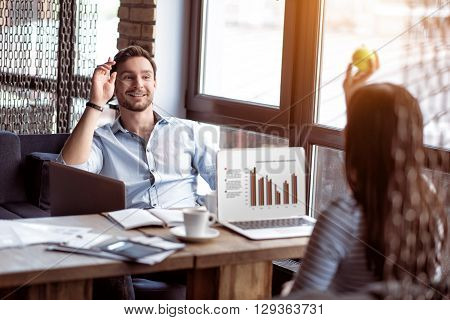 Your pitch. Cheerful delighted smiling colleagues sitting at the table and throwing a tennis ball while having fun