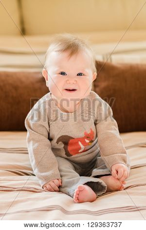 Laughing little child with blond hair and blue eyes wearing knitted sweater sitting on sofa and touching her leg. Happy childhood