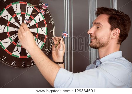 Hit the goal. Cheerful delighted handsome smiling man standing near dartboard and expressing gladness while playing darts