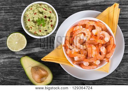 prawns on a white plate with guacamole sauce in a bowl on an old rustic table top view