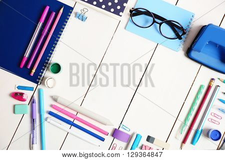 Flat lay of stationery on white wooden table background, copy space