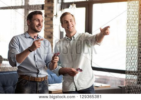 Hit the spot. Cheerful delighted handsome friends playing darts and smiling while spending time together