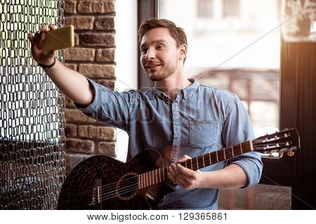 Just smile. Cheerful  content handsome man holding the guitar and smiling while making selfies
