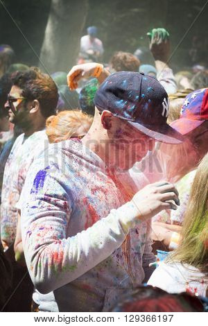 NEW YORK - APR 30 2016: A man in the crowd with colorful powder on his face celebrating the Holi Hai Festival of Colors hosted by NYC Bhangra in New York on April 30 2016.