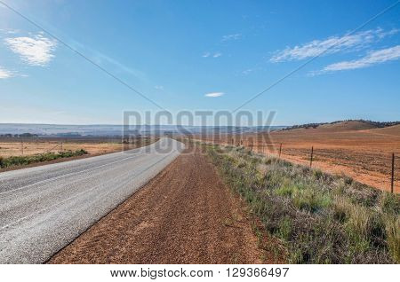 Road trip in Western Australia with native flora, red sand and wide open landscape under a blue sky with roadway.