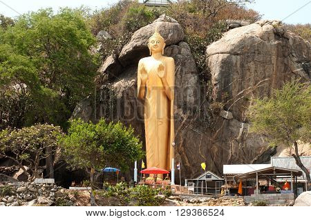PRACHUAP KHIRI KHAN,THAILAND-MAY 7,2016 : Outdoor Standing golden Buddha statue with a height 16 meters on Wat Khao Takiab is located at the foothill and facing to the sea, Hua Hin Beach, Pra Chuap Khi Ri Khun Province in Middle of Thailand.