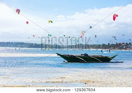 Boracay island, Philippines - FEB 01: kitesurfers enjoying wind power on Bulabog beach, small boat in foreground on February 01, 2016, Boracay island, Philippines.