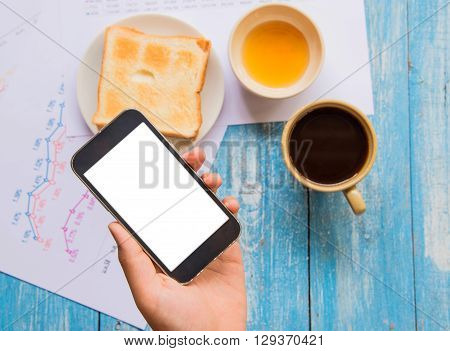 White display Smart phone in hand Toast Honey Coffee cup Graph data analysis placed on blue wooden floor.