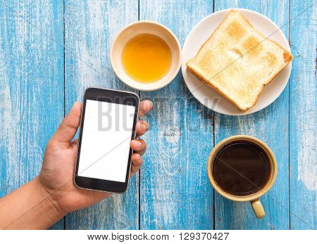White display Smart phone in hand Toast Honey Coffee cup placed on blue wooden floor.