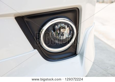 Closeup headlights of modern white car margin silver