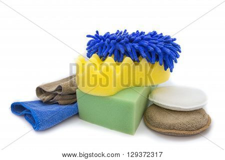 Yellow green sponges and blue mitts for washing and microfiber fabric with cleaner cloth on white background