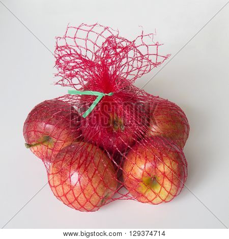 The shiny apples in the bright red net bag will make healthy snacks for whoever buys them.