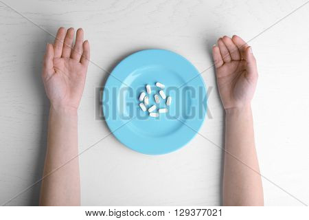 Female hands and plate filled with pills  on white table.