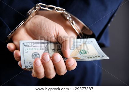 Man in handcuffs holding dollar banknotes behind the back, close up