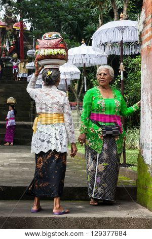 UBUD INDONESIA - MARCH 2 2016: Senior women with baskets on the heads during the celebration before Nyepi (Balinese Day of Silence) on March 2 2016 in Ubud Indonesia.