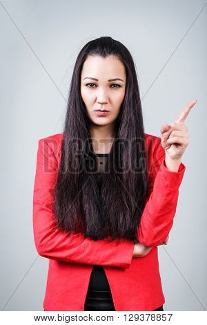 Young beautiful woman threaten finger on the gray background