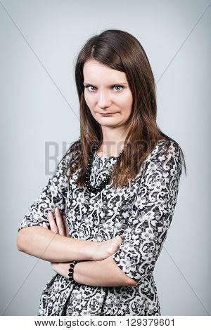 Attractive displeased woman looking strictly on gray background