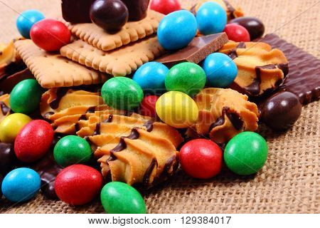 Heap of candies and cookies on jute burlap too many sweets concept of unhealthy food and reduction of eating sweets