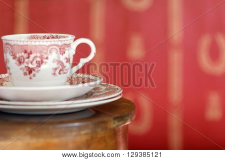 Coffee set made of white and red porcelain on a brown table and a red wall behind. Short depth of focus