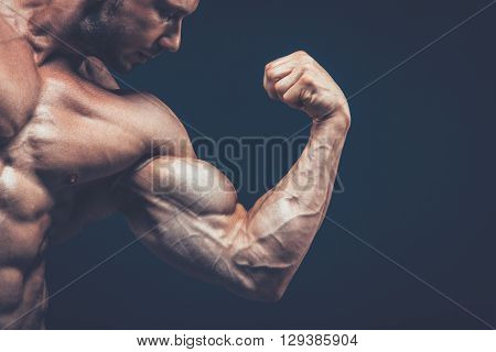 The athlete shows his beautiful body on black background