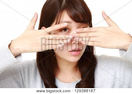 woman covering her face with hands peeping at the camera through her fingers