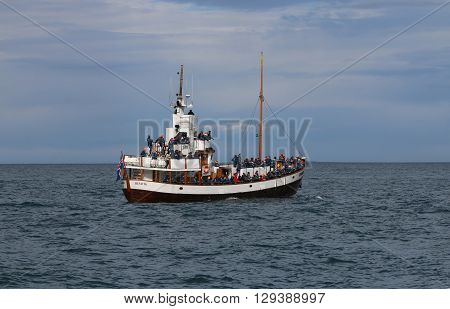 Husavik, Iceland - August 14, 2015: Tourists on a Boat at Whale Watching in Husavik.