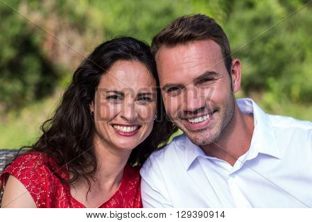 Close-up portrait of smiling young couple sitting in lawn