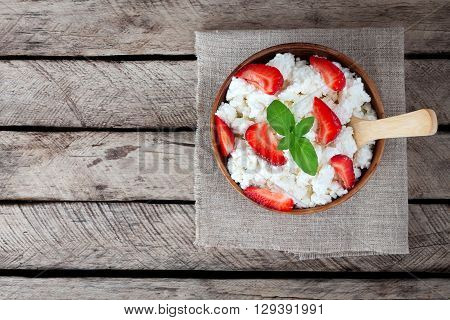 Bowl of cottage cheese strawberry wooden spoon on old wooden background. Healthy breakfast. Diet. Top view