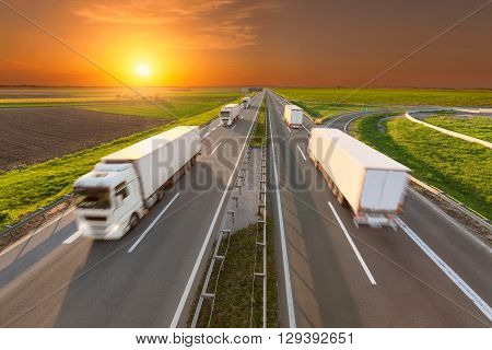 Temperature controlled trucks driving towards the sun. Fast blurred motion drive on the freeway at beautiful sunset. Freight scene on the motorway near Belgrade Serbia.