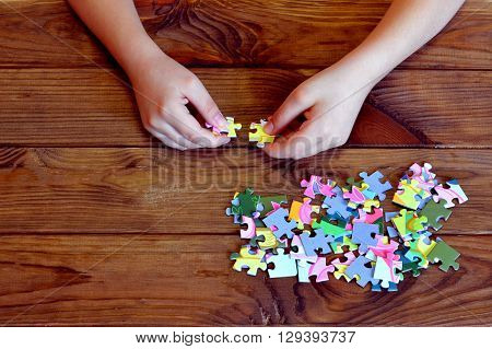 Child connects puzzles. A lot of puzzles on wooden table