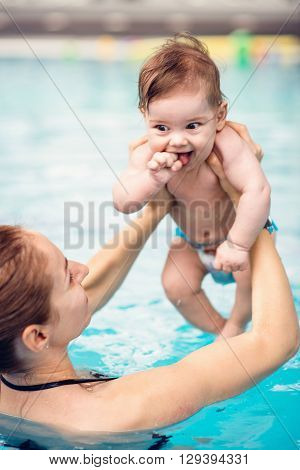 Cute baby boy with mother in swimming pool