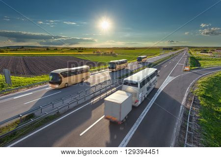 Many modern buses driving in blurred motion on the freeway at beautiful idyllic sunny day. Transport and travel scene on the motorway near Belgrade Serbia.