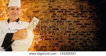 Composite image of friendly chef crossed arms on a brick and fire background