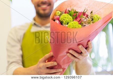 people, shopping, sale, floristry and consumerism concept - close up of happy florist man holding bunch wrapped in paper at flower shop