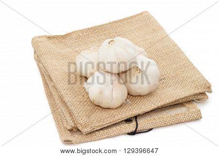 Garlic heap on cloth sack, isolate on white background