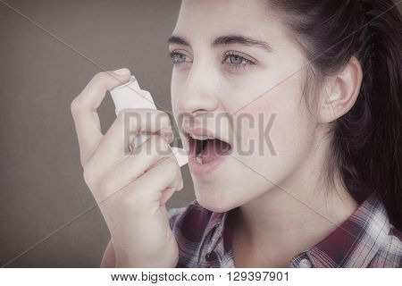 Woman having asthma using the asthma inhaler against grey background