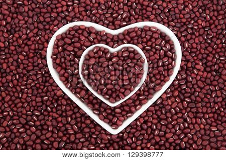 Adzuki bean health food in heart shaped porcelain dishes forming an abstract background.