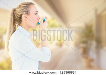 Beautiful blonde using an asthma inhaler against stylish outdoor patio area