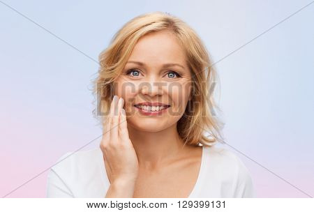 beauty, people and skincare concept - smiling woman in white shirt touching face over rose quartz and serenity gradient background